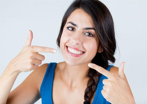 Woman pointing her clean teeth